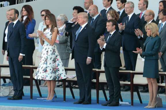Flanked by first lady Melania Trump, left, and French President Emmanuel Macron, right, President Donald Trump salutes U.S. troops during the annual Bastille Day military parade in Paris. This is the parade that inspired Trump to seek a similar event in Washington, D.C.