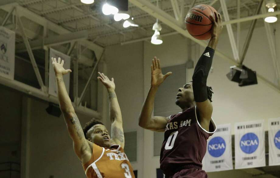 Texas A&M Aggies guard Jay Jay Chandler (0) goes up for a shot defended by Texas Longhorns guard Jacob Young (3) in the second half during the exhibition basketball game between the Texas Longhorns and the Texas A&M Aggies to benefit the Rebuild Texas Relief Fund at Tudor Fieldhouse in Houston, TX on Wednesday, October 25, 2017. Photo: Tim Warner, Freelance / For The Chronicle / Houston Chronicle