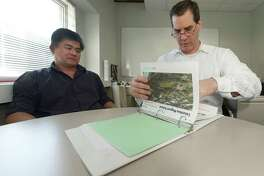 Norwalk building and facilities manager Alan Lo, who is in charge of construction for the city, and Jim Giuliano, president of Construction Solutions Group, the facility project manager for the new construction of the new South Norwalk school, go over renderings of the of the school, The New Columbus School, and the addition to Ponus Middle School, which will become a K-8 school.
