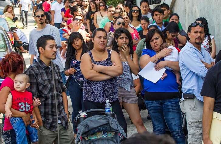 FILE - A line of people outside the Coalition for Humane Immigrant Rights in Los Angeles. A new study has found that, due to underfunding, politically motivated questions about immigration, and a new and untested online system, the 2020 census could seriously undercount Californians and potentially cost the state a Congressional seat. (AP Photo/Damian Dovarganes, File)