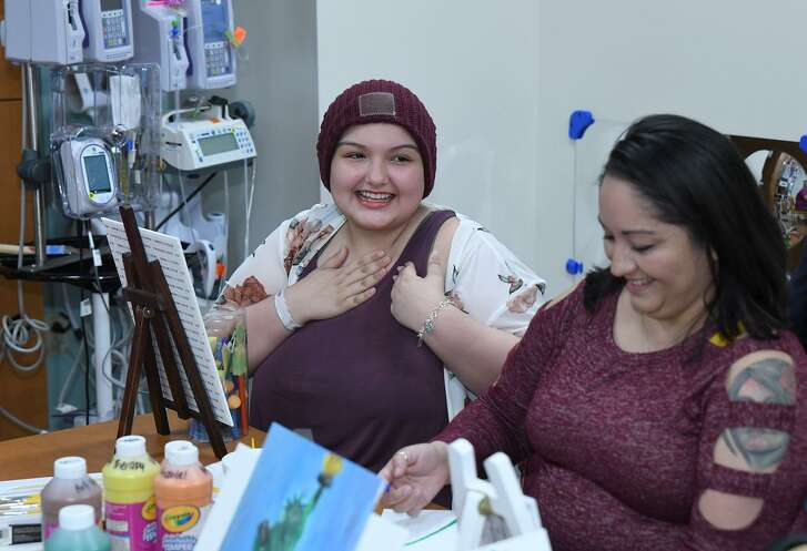 Emanii Younassoghlou, center, 14, a cancer patient at Methodist Children's Hospital, explains to Karen Pence, wife of Vice President Mike Pence, how creating art gives her joy and distracts her from her illness.