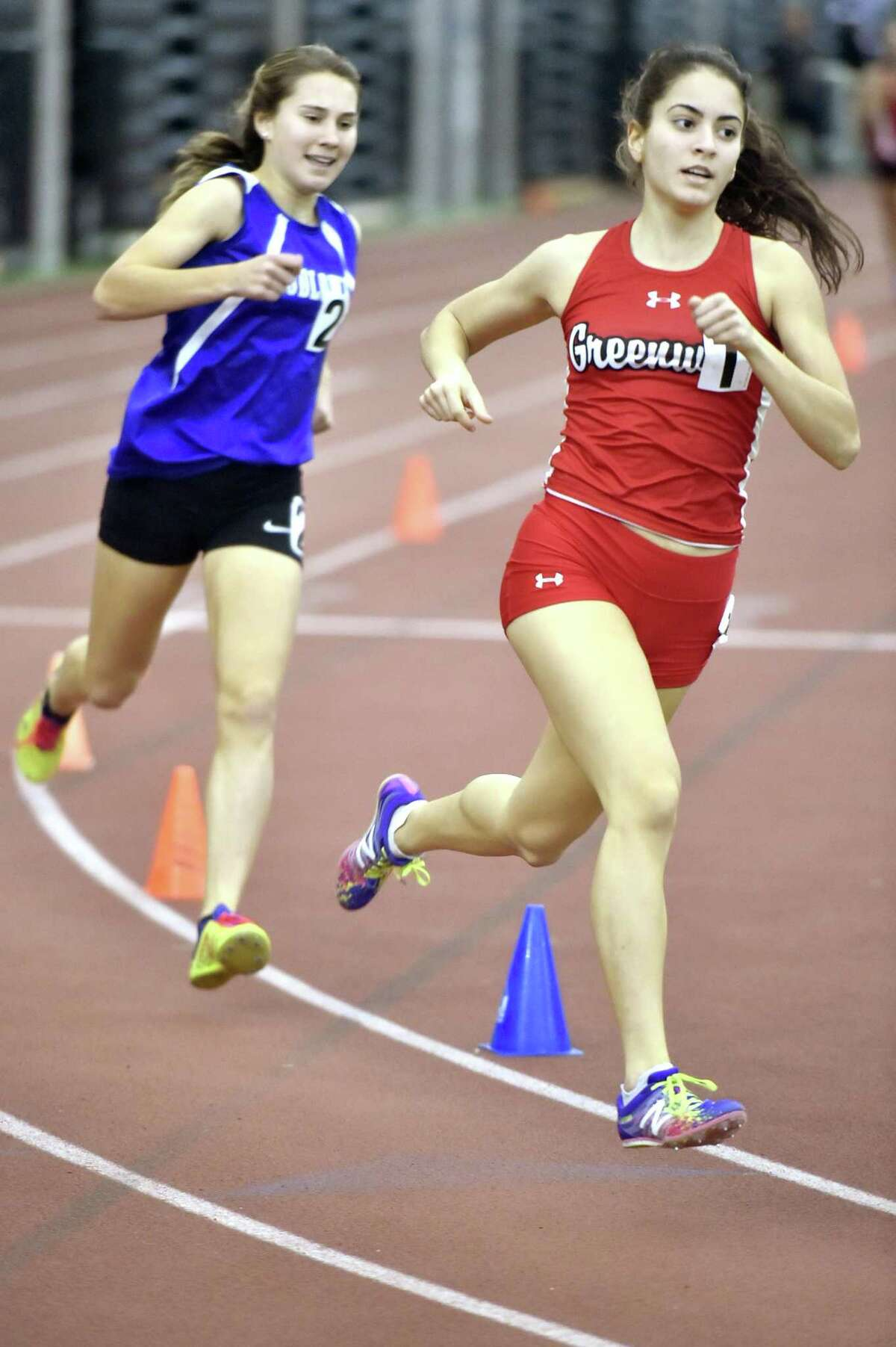 New Haven, Connecticut - Saturday, February 10, 2018: Girls 1000 meter run winner Emily Philippides of Greenwich H.S., right, runs ahead of eventual third place winner Alyssa Kraus of Fairfield-Ludlowe H.S. during the 2018 State Class LL Girls and Boys Indoor Track and Field Championship at the Floyd Little Athletic Center in New Haven .