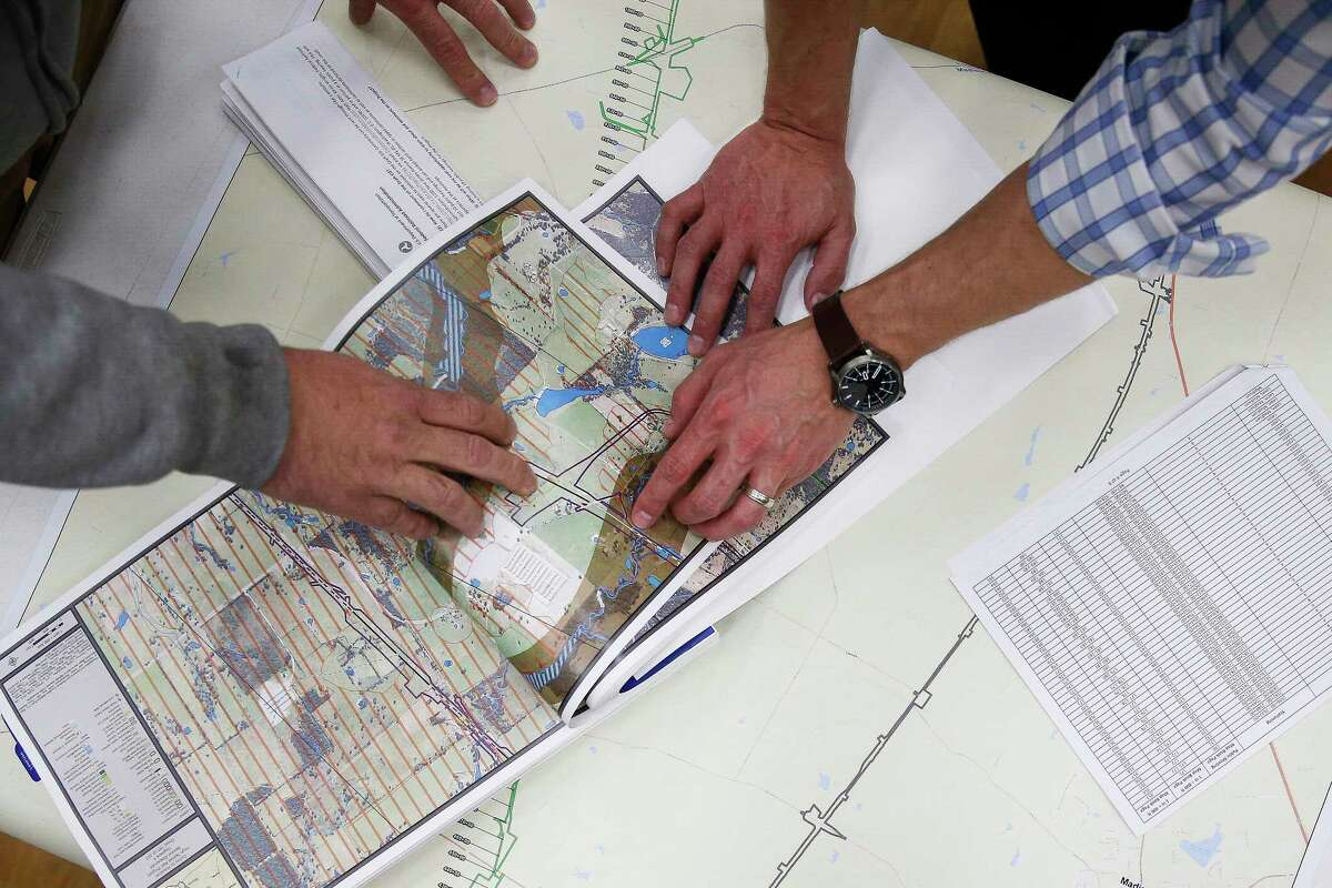 Matt Schiel, left, looks at a map of the Houston-to-Dallas bullet train going through the middle of his property with AECOM environmental planner Reggie Herman during a public hearing held by the Federal Railroad Administration to discuss the high-speed train on Feb. 5 in Cypress.