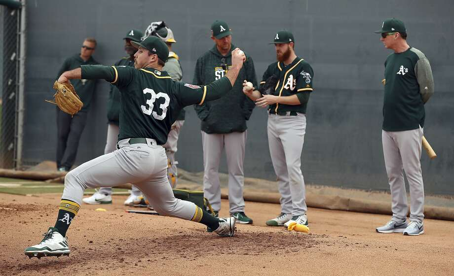 Oakland Athletics' Daniel Mengden (33) works during a spring training baseball practice as coach Bob Melvin, right, watches on Friday, Feb. 16, 2018 in Mesa, Ariz. (AP Photo/Ben Margot) Photo: Ben Margot, Associated Press