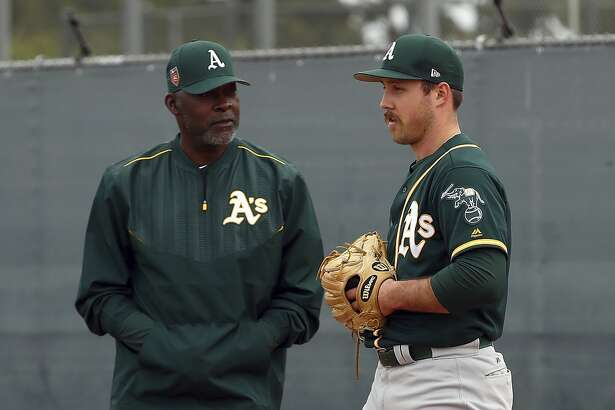 Oakland Athletics special instructor Dave Stewart, left, speaks with pitcher Daniel Mengden during a spring training baseball practice on Friday, Feb. 16, 2018 in Mesa, Ariz. (AP Photo/Ben Margot)