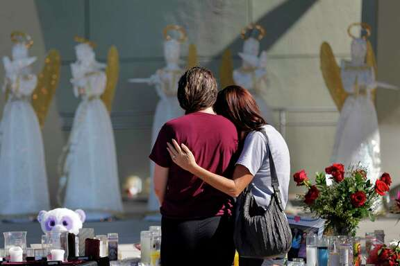 "People visit a memorial Friday in Parkland, Fla. ""I was hiding in a closet for two hours. It was about guns. You weren't there, you don't know how it felt,"" student Carly Novell told a gun-rights activist."