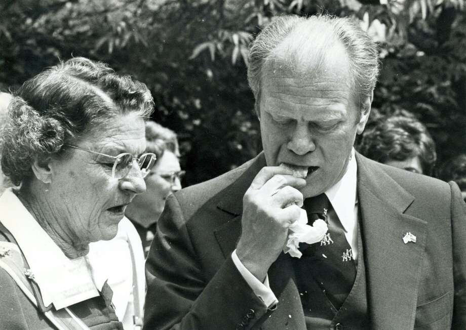 In a Express-News file photo of President Gerald Ford attempts to eat a tamal, shuck and all, April 9,1976. Photo: File Photo / Express-News / SAN ANTONIO EXPRESS-NEWS