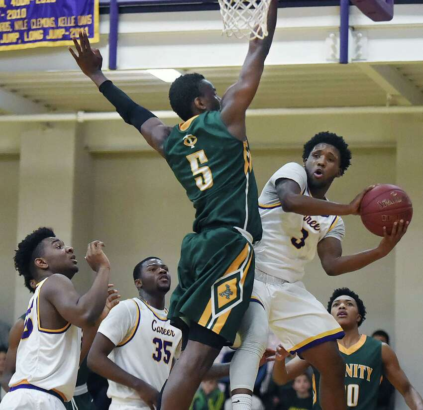 Career's Tamar Williams looks to make a pass around Contavio Dutreil of Trinity Catholic-Stamford in a non-conference game, Friday, Feb. 16, 2018, at the Hill Regional Career High School in New Haven. Trinity Catholic won, defeats Career, 64-61.