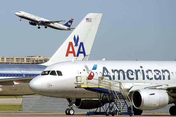 A U.S. Airways jet takes off over an old and new paint designs on American Airlines planes at the DFW International Airport, TX, Monday, May 5, 2014.  (Star-Telegram/Max Faulkner)