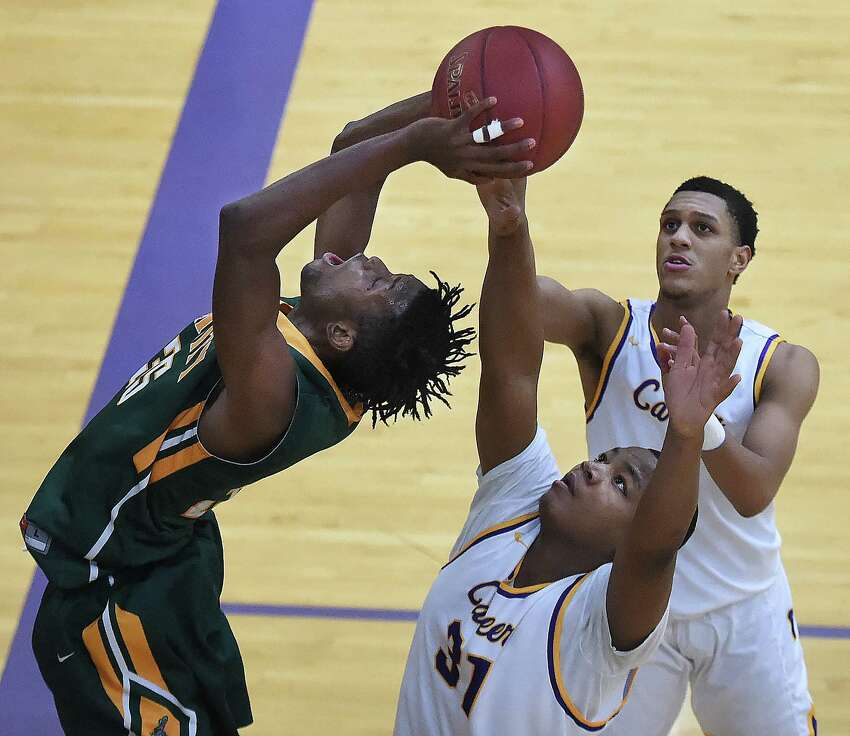 Trinity Catholic-Stamford's Dimitry Morse elevates at the hoop as Career's Nate Morrison (31) and Savee'on Avery (4) in a non-conference game, Friday, Feb. 16, 2018, at the Hill Regional Career High School in New Haven. Trinity Catholic won, 64-61.