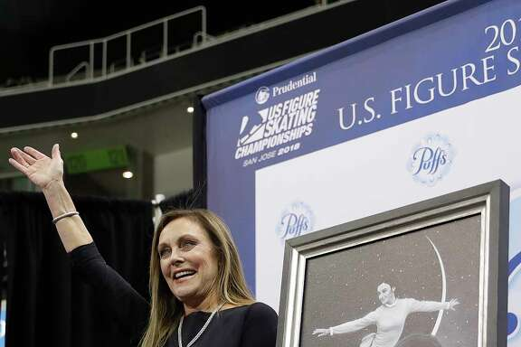 Peggy Fleming waves next to a painting of her at the U.S. Figure Skating Championships in San Jose, Calif., Wednesday, Jan. 3, 2018. (AP Photo/Marcio Jose Sanchez)