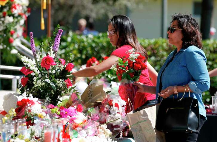 Mourners visit a memorial Friday for the victims of the Majory Stoneman Douglas High School in Parkland, Fla. Nikolas Cruz, the alleged shooter, confessed to the killings, a police report said.