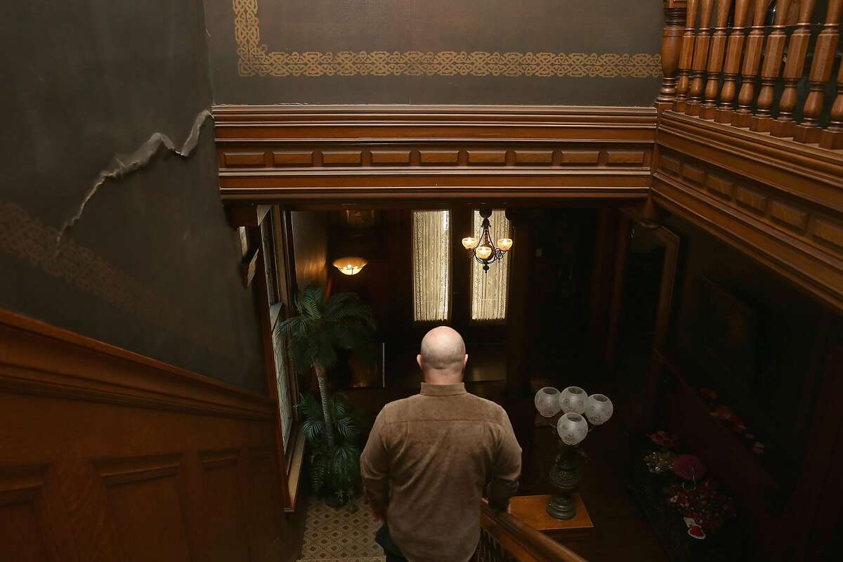 The great grandchild of William and Bertha Haas, John Rothmann walks down the stairway to the first floor where the crack on left is from the 1989 earthquake at the Haas Lilenthal house which has recently been restored on Thursday, February 15, 2018, in San Francisco, Ca.