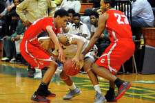 Bassick's Kevin Crawford gets pressure from Central's DJ Fulton, left, and Raj Walker during their game Friday night in Bridgeport.