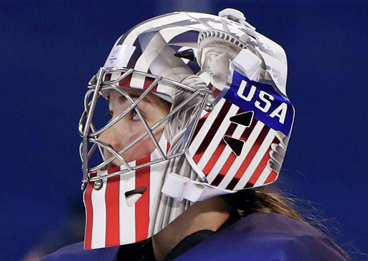 In this Feb. 13, 2018 photo, Goalie Nicole Hensley, of the United States, wears a patriotic themed mask during the preliminary round of the women's hockey game against the team from Russia at the 2018 Winter Olympics in Gangneung, South Korea. Goaltenders are the only players in Olympic hockey allowed to get creative with decorating their helmets. Their teammates are stuck with helmets featuring basic colors, uniform numbers and a small flag decal representing their country. (AP Photo/Matt Slocum)