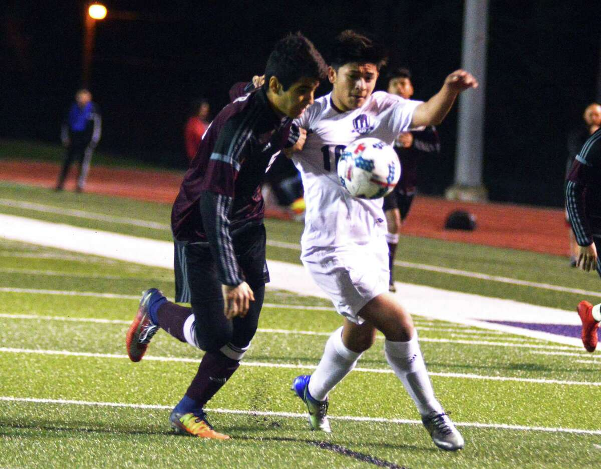 Willis forward Erick Gallaga tries to fight off a defender during a district soccer match at Yates Stadium in Willis on Friday night.