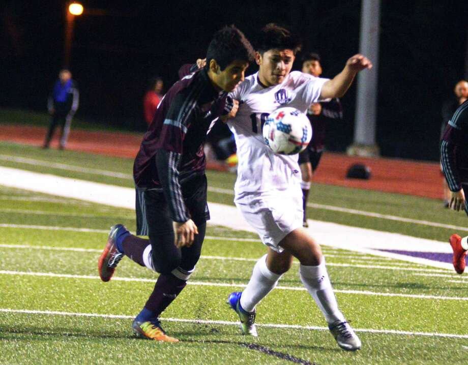 Willis forward Erick Gallaga tries to fight off a defender during a district soccer match at Yates Stadium in Willis on Friday night. Photo: Keith MacPherson
