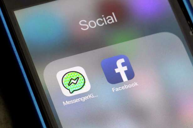 Facebook and Facebook's Messenger Kids app icons are displayed on an iPhone in New York, Friday, Feb. 16, 2018. Messenger Kids lets kids under 13 chat with friends and family. It displays no ads and lets parents approve who their children message.  (AP Photo/Richard Drew)