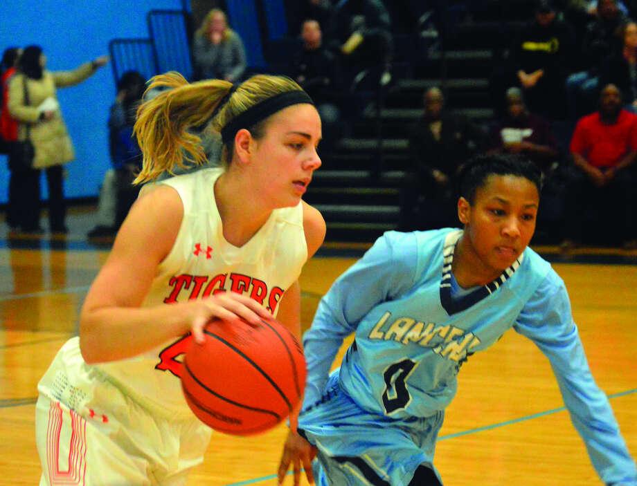 Edwardsville senior forward Rachel Pranger drives past Belleville East guard Kaylah Rainey in the first quarter.