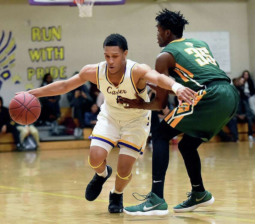 Career sophomore guard Savee'on Avery drives past Trinity Catholic senior forward Dimitry Moise in the first half of a non-conference game, Friday, Feb. 16, 2018, at the Hill Regional Career High School in New Haven. Trinity Catholic-Stamford won, 64-61.
