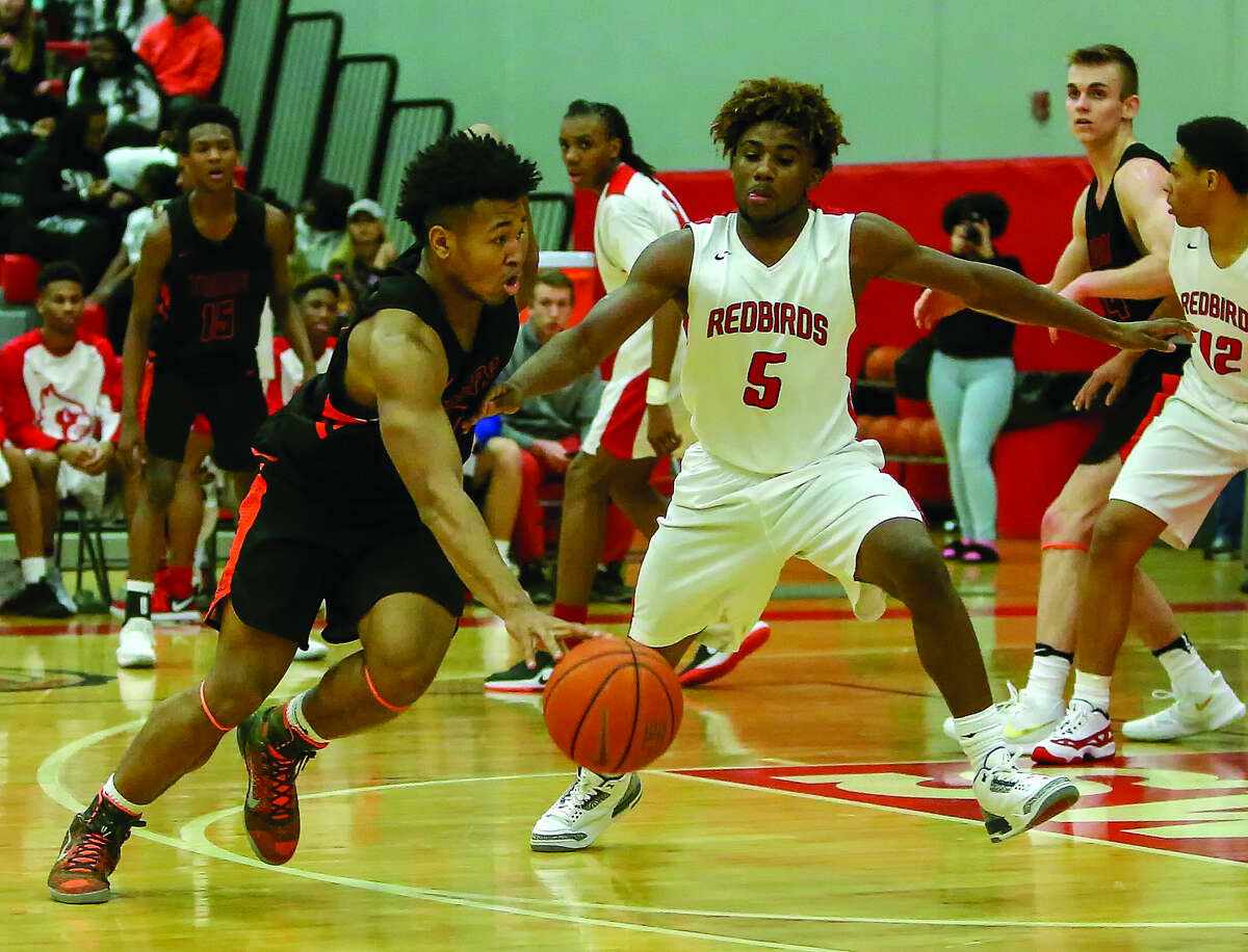 Edwardsville's RJ Wilson (40) drives past Alton's Darrell Smith (5) during Friday's Southwestern Conference game in Alton.
