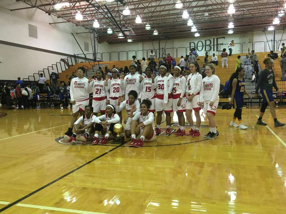 The Crosby Lady Cougars pose after beating the Elkins Lady Knights on Feb. 16 at Dobie High School in Pasadena to win the Area championship. Some players hold up three fingers signifying the team's advancement to the third round of the playoffs, the regional quarterfinals. Photo: Elliott Lapin