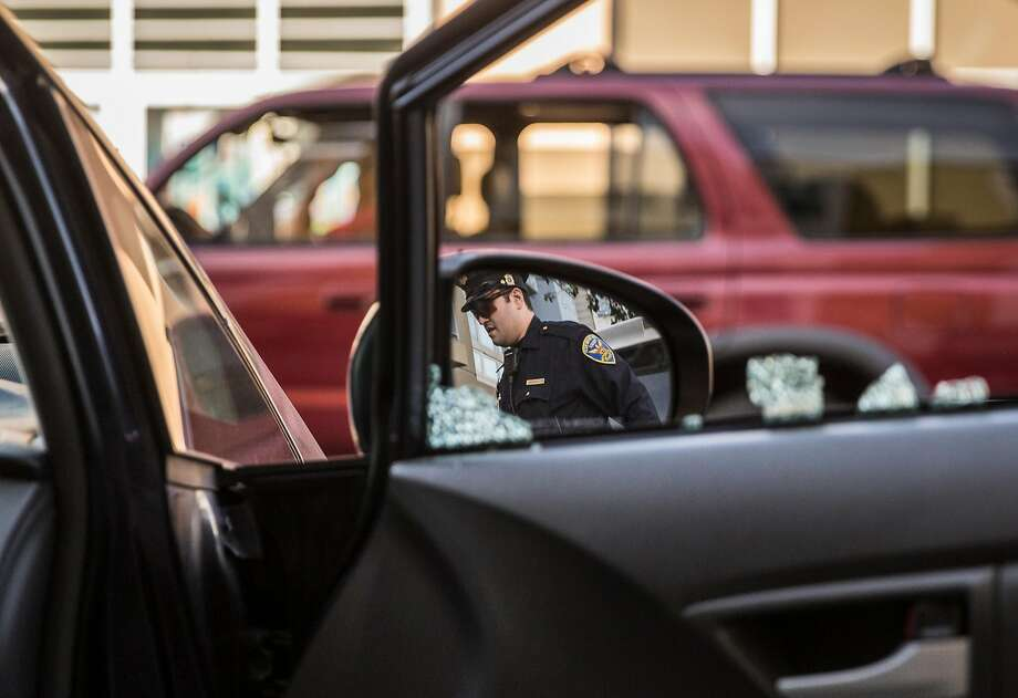 As he investigates a car break-in near 24th Street and Potrero Avenue in early February, San Francisco police Officer Robert Clendenen is reflected in Michael Lech's rearview mirror. Photo: Jessica Christian, The Chronicle