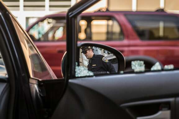 Mission District San Francisco Police Officer Robert Clendenen is seen in the reflection of Michael Lech's rear view mirror as he investigates a car break-in near Potrero Street and 24th Avenue Thursday, Feb. 1, 2018 in San Francisco, Calif.