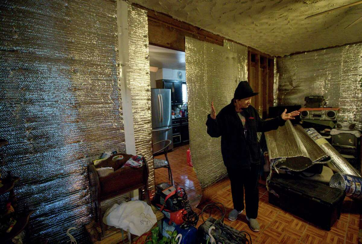 """A woman walks through the flood-damaged living room of her home, where she was still living months after Hurricane Harvey """"I lost everything,"""" she said of the storm. A church donated drywall to help with repairs."""