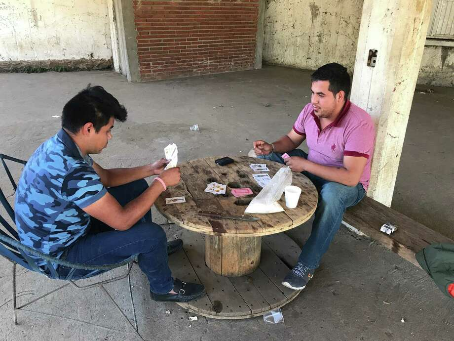 Gustavo Cortez plays cards with his cousin Cesar Cortez as they began their shift to help protect Aguacate Sur, Mexico. Much of the funding for their security force comes from avocado growers.  Photo: Alfredo Corchado, MBR / Dallas Morning News