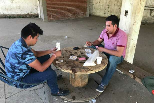 Gustavo Cortez plays cards with his cousin Cesar Cortez as they began their shift to help protect Aguacate Sur, Mexico. Much of the funding for their security force comes from avocado growers.