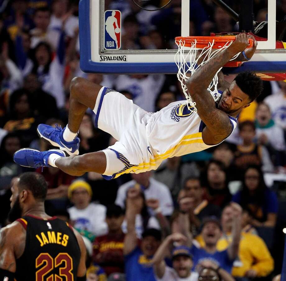 Jordan Bell hangs on the rim on a dunk in the second half as the Golden State Warriors played the Cleveland Cavaliers at Oracle Arena on Monday, December 25, 2017. Photo: Carlos Avila Gonzalez / The Chronicle