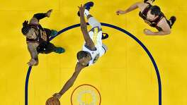 Kevin Durant (35) puts up a shot between Jae Crowder (99) and Kevin Love (0) in the second half as the Golden State Warriors played the Cleveland Cavaliers at Oracle Arena in Oakland, Calif., on Monday, December 25, 2017.