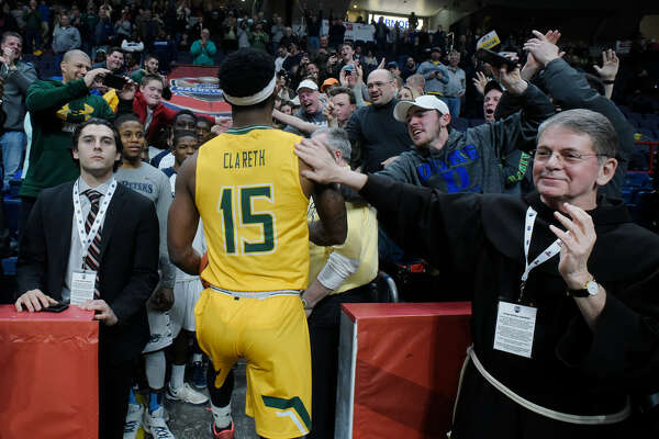 The Siena crowd, including college president Br. Edward Coughlin (right), congratulated Nico Clareth after his memorable performance against Monmouth in last year's MAAC Tournament semifinal. (Paul Buckowski/Times Union)