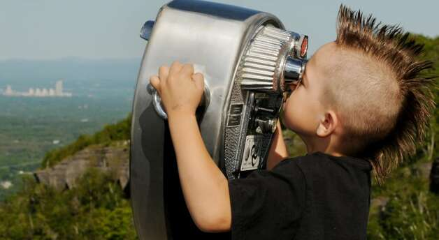 Trevor Ballew, 6, of Ballston Spa, looks through one of the telscopic viewers Sunday along the retaining wall at the Overlook at John Boyd Thacher State Park. (Luanne M. Ferris / Times Union) Photo: LUANNE M. FERRIS