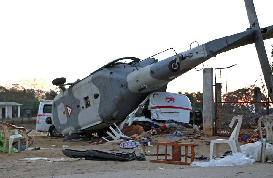 A toppled military helicopter rests on a crushed van in Santiago Jamiltepec in Mexico's Oaxaca state. Photo: PATRICIA CASTELLANOS, AFP/Getty Images