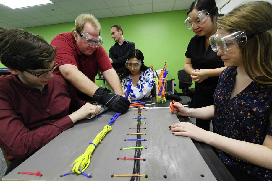 Lone Star College engineering students Sean Palmer, James Philippi, Maria Gonzale, Daniel Vasek, instructor Yiheng Wang and student Fancesla Liso are building a prototype zip tie cutter tool designed for use during spacewalks that will be tested at NASA's Johnson Space Center later this year. Photo: Tony Gaines/ HCN, Staff / Houston Chronicle