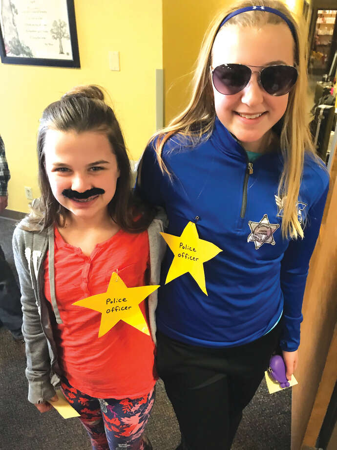 "Grace Deakos and Maggie Pifer, working the ""Jail"" Booth at Mission. At right, Ellie Luchtefeld and her 7th grade buddy Maddie Burkart check out the Mission Carnival at St. Boniface. Photo: For The Intelligencer"