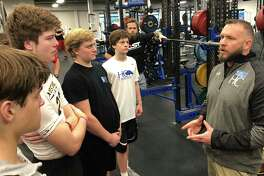 Houston Christian football coach David Nelson addresses players in the school's training facility during an offseason workout. Nelson was hired as head coach this month after a year of mission work in Kenya.
