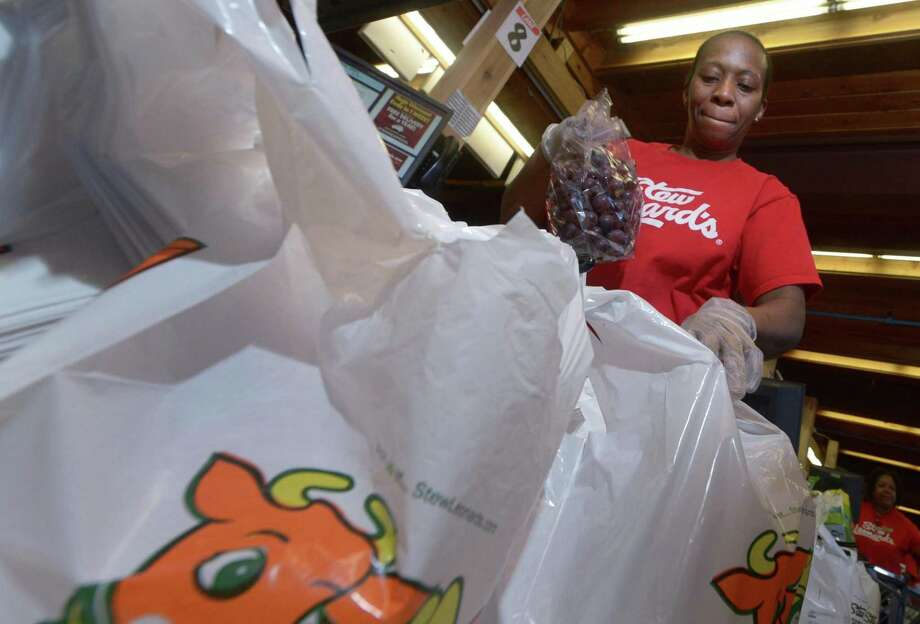 Cashier Milmene Joseph bags groceries in Stew Leonard's iconic plastic bags into her cart at the store Wednesday in Norwalk. Some Common Council members are considering whether plastic bags should be banned in the city. Photo: Erik Trautmann / Hearst Connecticut Media / Norwalk Hour