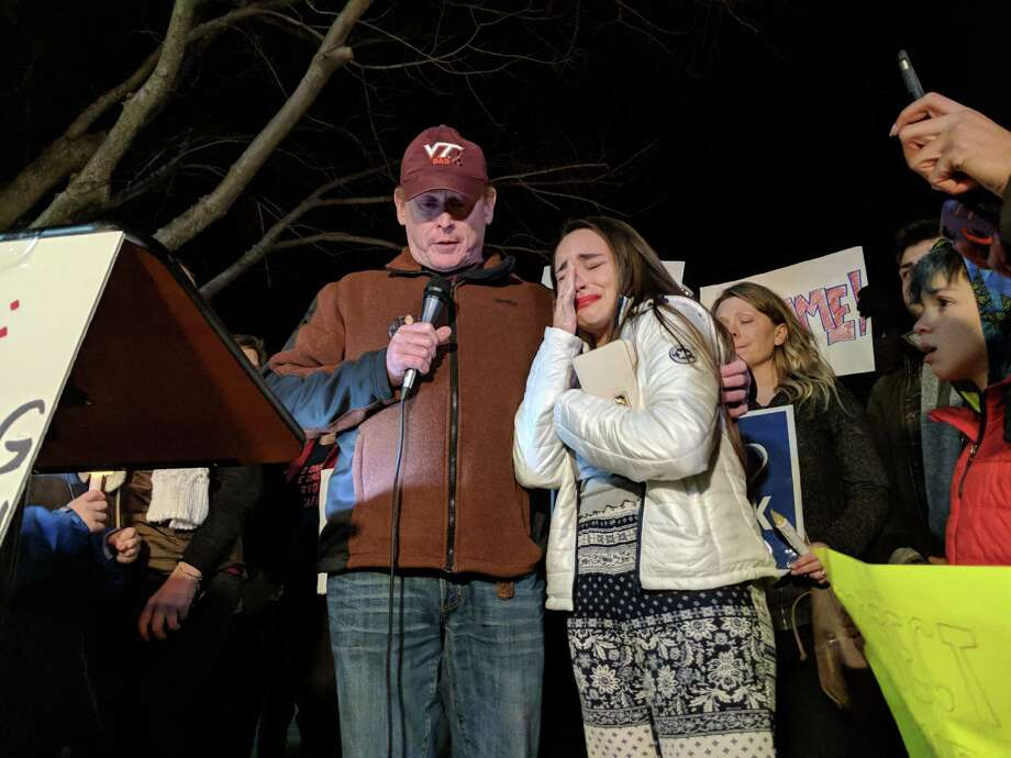 At a gathering outside the National Rifle Association's headquarters in Fairfax, Virginia, Gillian Beard cries as she is held by speaker Peter Reed, whose daughter was killed during the 2007 Virginia Tech shootings. Photo: Washington Post Photo By Clarence Williams / The Washington Post