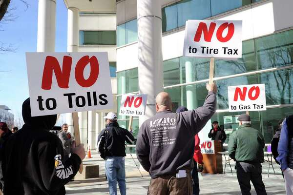 Protestors hold signs against tolls, a tire tax and a gas tax during a protest held in front of the Stamford Goverment Center, Stamford SaturdayRoughly 75 people attended the protest that was accompanied by a caravan of trucks circling the center honking their horns in support of the protestors. Gov. Dannel P. Malloy wants legislators to pass measures including electronic tolls, an increase in state gasoline taxes and a new tax on the sale of tires, to pay for Connecticut's transportation system that he says is facing a serious fuding crisis.