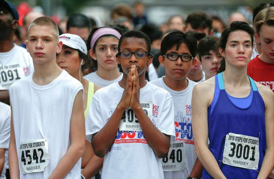 Ikeobasi Ezike, 13, (center) takes in a special blessing from Daniel Cardinal DiNardo before running in the Archdiocese of Galveston-Houston's 13th annual Steps-for-Students 5K Run/Walk Saturday, Feb. 17, 2018, in Houston. Over 12,000 runners/walkers hit the streets of downtown for the event which benefits the network of 59 Catholic schools in the Archdiocese of Galveston-Houston, the largest private school systems in Texas. Photo: Steve Gonzales, Houston Chronicle / © 2018 Houston Chronicle