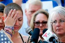 "Marjory Stoneman Douglas High School student Emma Gonzalez reacts during her speech at a rally for gun control at the Broward County Federal Courthouse in Fort Lauderdale, Florida on February 17, 2018. A student survivor of the Parkland school shooting called out US President Donald Trump on Saturday over his ties to the powerful National Rifle Association, in a poignant address to an anti-gun rally in Florida. ""To every politician taking donations from the NRA, shame on you!"" said Emma Gonzalez, assailing Trump over the multi-million-dollar support his campaign received from the gun lobby -- and prompting the crowd to chant in turn: ""Shame on you!""   / AFP PHOTO / RHONA WISERHONA WISE/AFP/Getty Images"