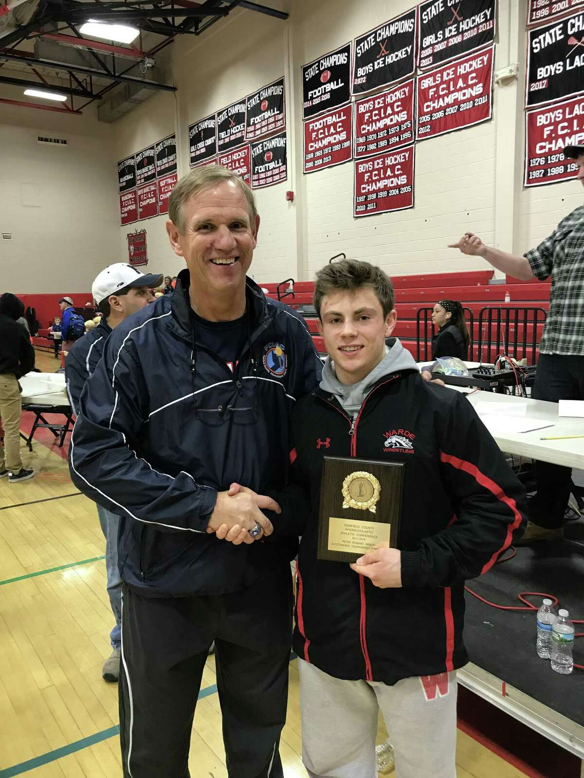 FCIAC Executive Director Dave Schulz shanks hands with 2018 FCIAC Most Outstanding Wrestler Alex Steele of Warde after Steele won the 132 pound championship.