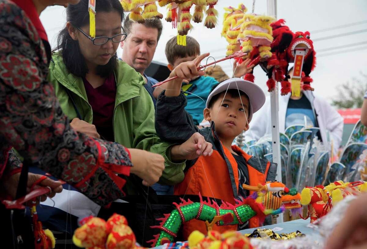 A young boy plays with a Chinese toy during a Lunar New Year celebration at the Chinese Community Center on Saturday, Feb. 17, 2018, in Houston.