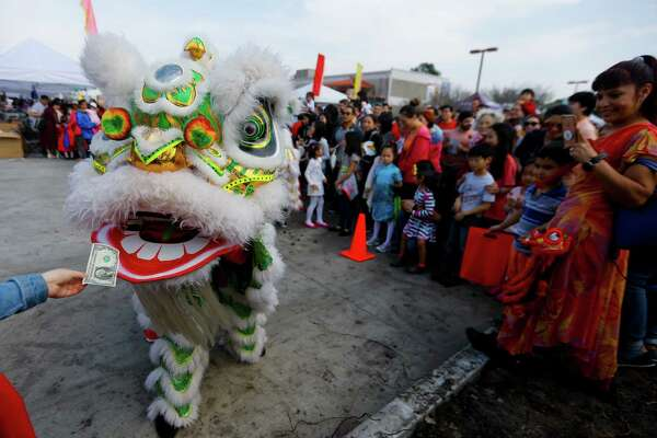 A dollar is given to one of the lions during a Lunar New Year celebration at the Chinese Community Center on Saturday, Feb. 17, 2018, in Houston.