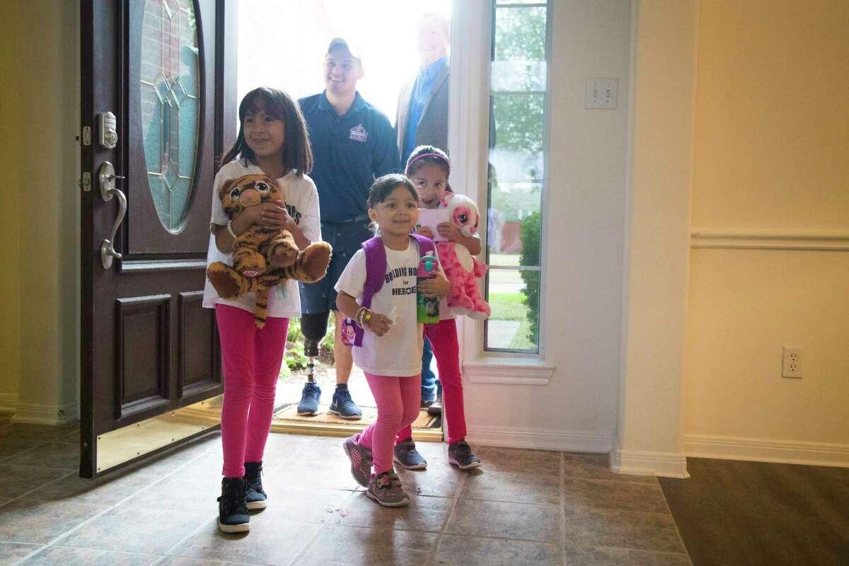 Michael Villagran enters his new home with his daughters, Natalia Villagran, 7, Carolina Villagran, 3, and Alyssa Villagran, 5.