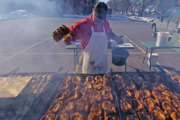Times Union Staff photo by Skip Dickstein      Harry Parkington of Brooks Barbecue bastes his chicken in the church parking lot at the benefit barby at Bethany Reformed Church in Albany, New York February 18, 2004.  The weather cooperated with the barbecue.