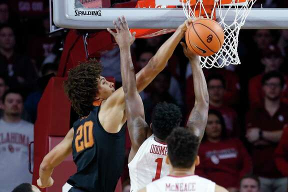 Texas forward Jericho Sims (20) leaves Oklahoma guard Rashard Odomes (1) with a feeling of rejection in the first half of the Longhorns' win Saturday in Norman, Okla.